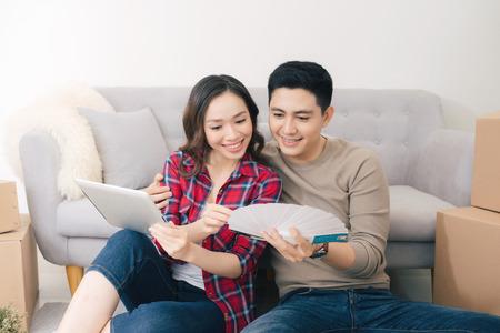 若いアジアのカップルが床に座って、新しい家の青写真を見ています。