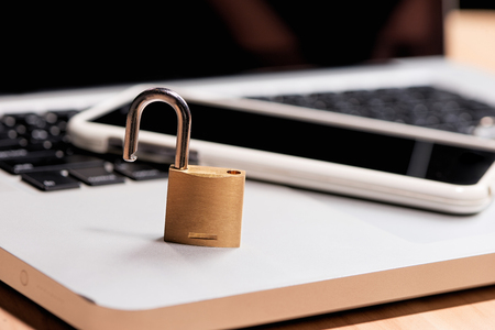 Smartphone and padlock is lying on a laptop keyboard Stock Photo