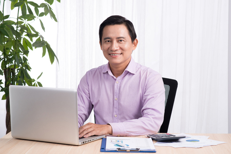 Smiling businessman at his desk with laptop and documents in his office Stock fotó