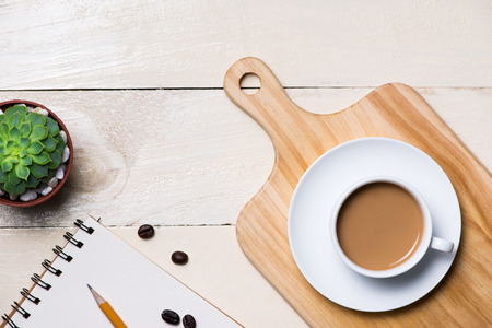 Image of the blank page of small note with pencil, a cup of coffee on wooden background