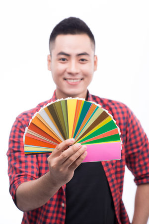Happy asian male graphic designer holding color fan in his hand Stok Fotoğraf