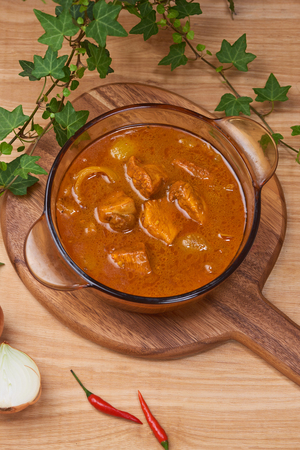 Tasty dinner with chicken curry in bowl on wooden background Stock Photo