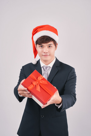 Smiling asian businessman in santa hat presenting gift isolated on white Stock Photo