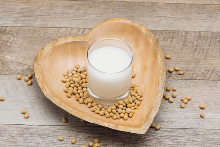Glass with soy milk and soy bean on wooden heart shape plate Stock Photo