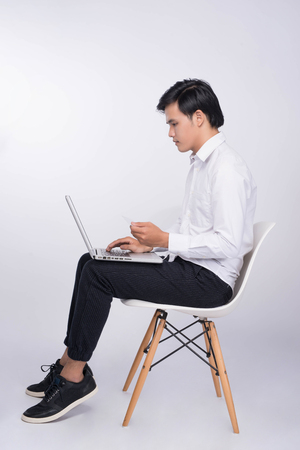 Smart casual asian man seated on chair, using laptop in studio background 스톡 콘텐츠
