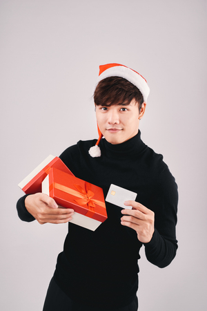 Young handsome asian man with santa hat giving a red gift and holding credit card. Stock Photo
