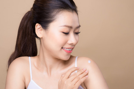 Clean fresh skin concept. Young asian woman putting cream on her shoulder