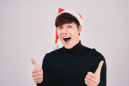 A young successful man with santa hat with his arms raised celebrating Christmas Holiday.