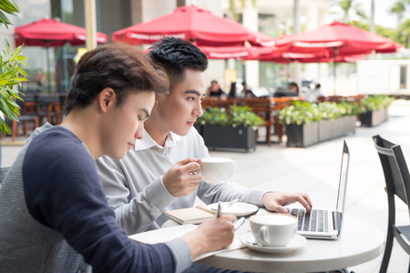 Portret van twee Aziatische bedrijfsmensen die in een koffiewinkel samenkomen