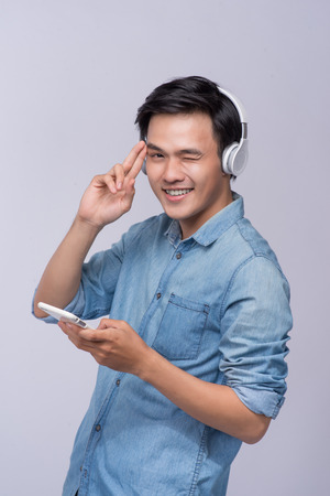 Handsome young man wearing headphones and holding mobile phone while standing against grey