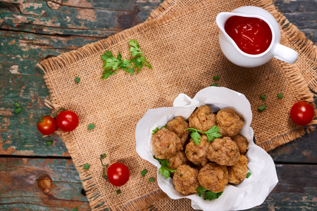 Minced fried fish balls with cucumber cressl on a white background with chilli sauce  . Selective focus