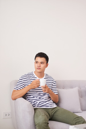 Young asian man sitting on the couch drinking a cup of coffee