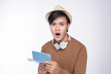 Surprised asian male tourist holding passport over grey background