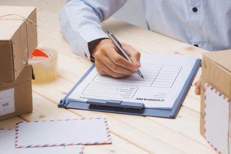 宅配便は、テーブルで小包の間で配達領収書にメモを作ります 写真素材