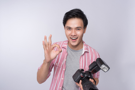 Young asian photographer holding digital camera, while working in studio Stock Photo - 91694602