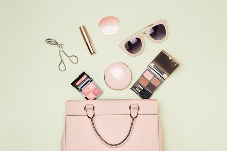 Makeup products with cosmetic bag on color background