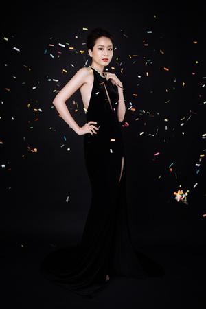 Aziatische vrouw met mode make-up in luxe zwarte jurk terwijl confetti vallen op haar.