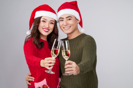 Asian couple wearing christmas hat and dress holding champagne glass Stock Photo