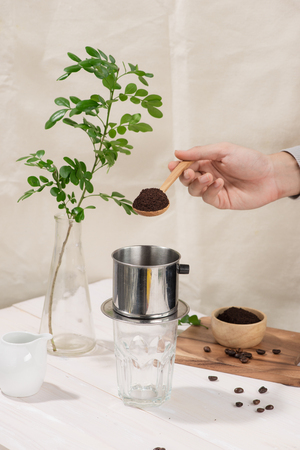 Coffee dripping in vietnamese style on wooden table Stock Photo