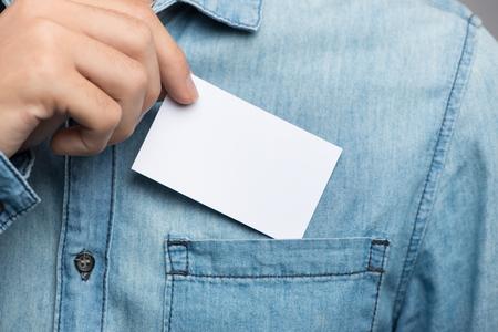 Jeune homme qui prend une carte de visite vide de la poche de sa chemise Banque d'images - 91785703