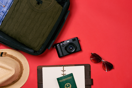 Preparation for travel concept - passport, camera, hat, chrismas decorations on red background Stock Photo