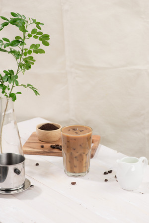 Coffee with milk and ice on natural wooden Фото со стока