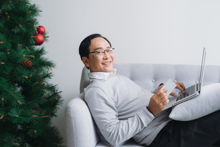 Senior asian man shopping using latop and credit card by the christmas tree