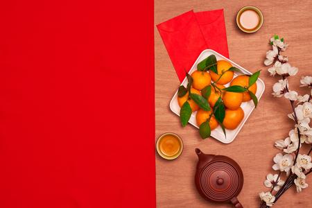 상위 뷰 액세서리 중국 새 해 축제 decorations.orange, 잎, 나무 바구니, 빨간 패킷, 빨간색 배경에 매 화 꽃.