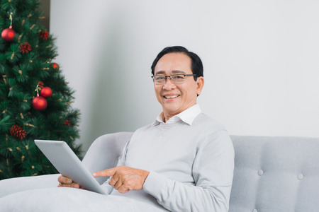 Senior man is using a digital tablet and smiling while resting on couch at home
