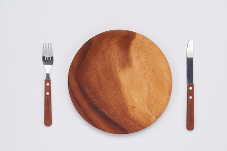Empty wooden dish with knife and fork on white background, Top view Stock Photo