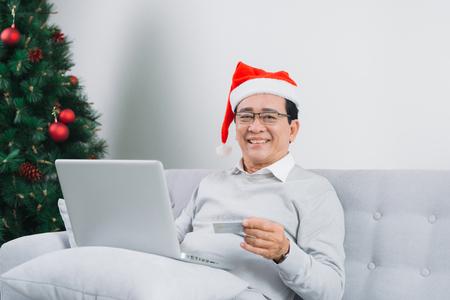 Senior man wearing santa hat shopping using latop and credit card by the christmas tree Stock Photo