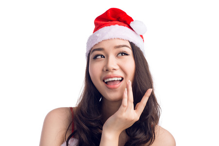 Christmas Woman. Beauty Asian Model Girl in Santa Hat Thinking Something.