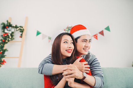 Christmas Asian Couple.Happy Smiling Family at home celebrating. New Year People