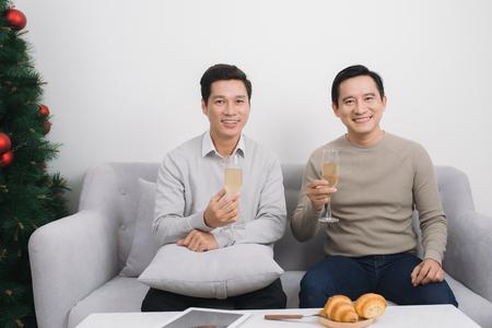 クリスマスの間に自宅でシャンパングラスを持つセーターを着た2人のアジア人男性