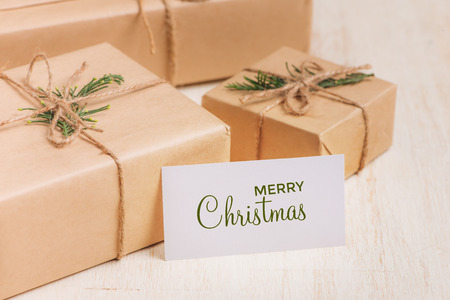 Christmas or New year gift boxes collection wrapped in kraft paper on wood background.