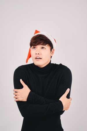 Winter portrait of young asian man with santa hat in snow.