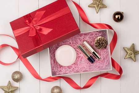 Cosmetic products in gift box on wooden background
