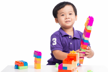 Kid boy playing with blocks from toy constructor isolated