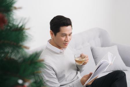 クリスマスの間に家でお茶を飲んでセーターを着たアジア人男性