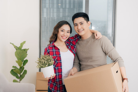 Loving couple enjoys a new apartment and keep the box in hands  Foto de archivo