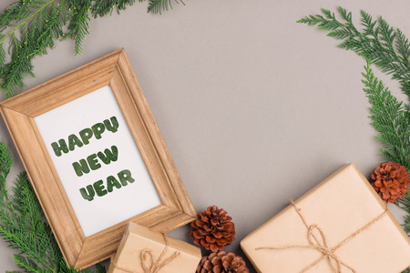 Happy New Year. Gift boxes collection wrapped in kraft paper and blank photo frame for text.