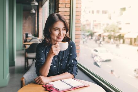 Portrait der glücklichen jungen Geschäftsfrau mit Becher in den Händen , die Kaffee am Morgen im Restaurant trinkt Standard-Bild