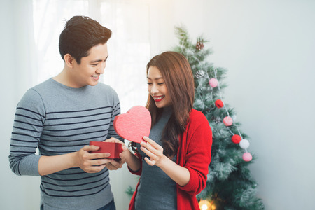 Christmas Asian Couple. A handsome man giving her girlfriend/wife a gift at home celebrating New Year People Stock Photo