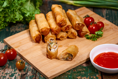 Vietnamese food. Delicious homemade spring rolls on wooden table. Zdjęcie Seryjne