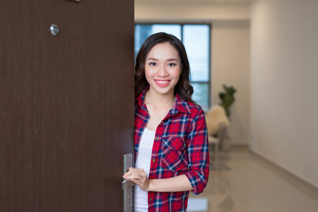 Cheerful asian awoman inviting people to enter in home
