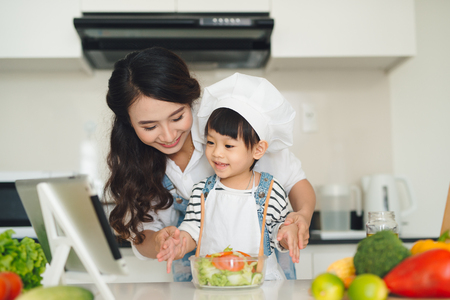 Mother with her daughter preparing lunch in the kitchen and enjoying together.
