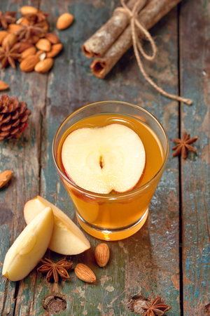 Hot drink of apple tea with cinnamon stick. Hot drink with apples for autumn or winter.