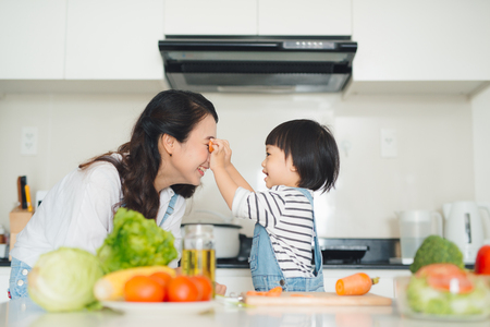 Happy family in the kitchen. Mother and child daughter are preparing the vegetables and fruit. Banque d'images