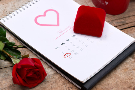 Calendar showing the date 14th of February. Red rose, hearts and gift box on wooden table. Stok Fotoğraf