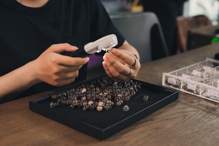 Handen van vrouwelijke juwelenontwerper die haar werk met vergrootglas bekijken